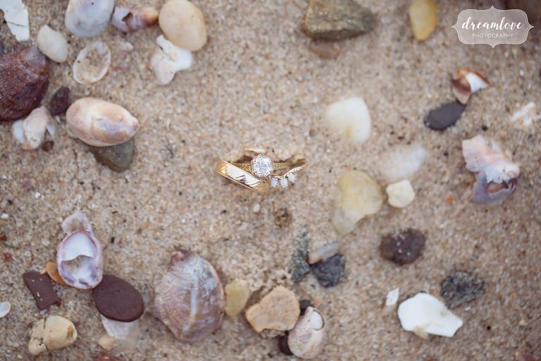 The wedding rings with opal and a hexagon diamond set in sand on the beach at this NY camp wedding.