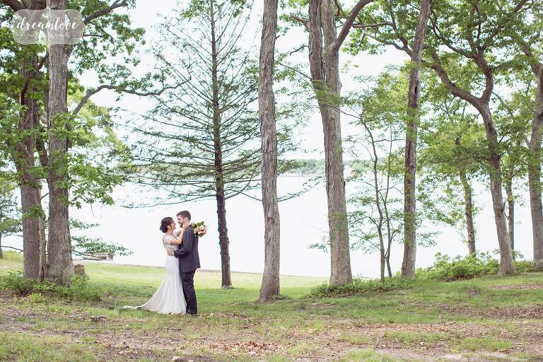 The bride and groom stand in the trees for this woodsy NY camp wedding.
