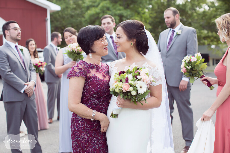 The bride's mother looks at her daughter before wedding ceremony at this NY camp wedding.