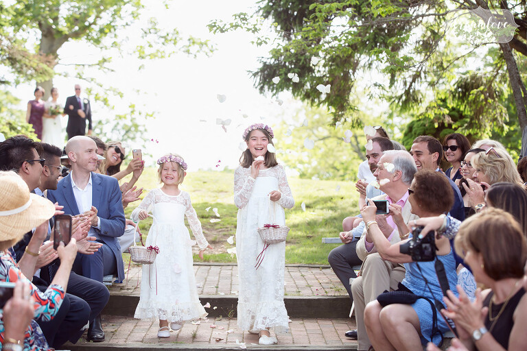 Flower girls in long dresses and lace sleeves toss petals at this outdoor ceremony.