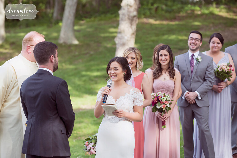 The bride reads her vows during this outdoor NY camp wedding.