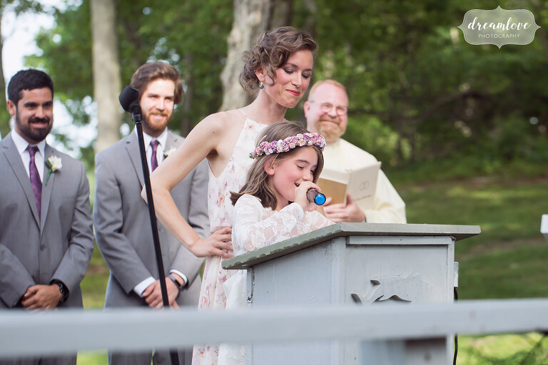 The flower girl does a reading during this outdoor ceremony in NY.