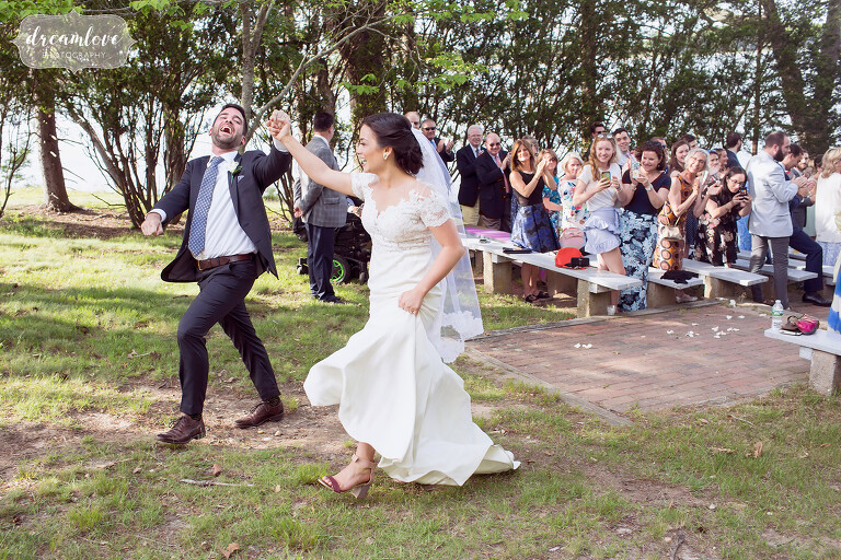 A happy photo of the bride and groom exiting ceremony at this NY camp wedding.