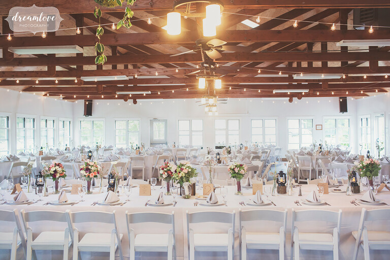 Simple decorations of single flowers in antique vases and wooden boxes at this NY camp wedding on Shelter Island.