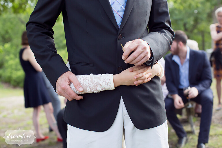 The flower girl wraps her arms around her dad's waist in this unique wedding photo.