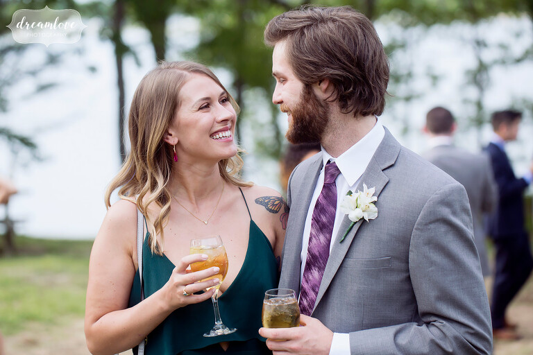 Wedding guests enjoy cocktails outside at this NY camp wedding.