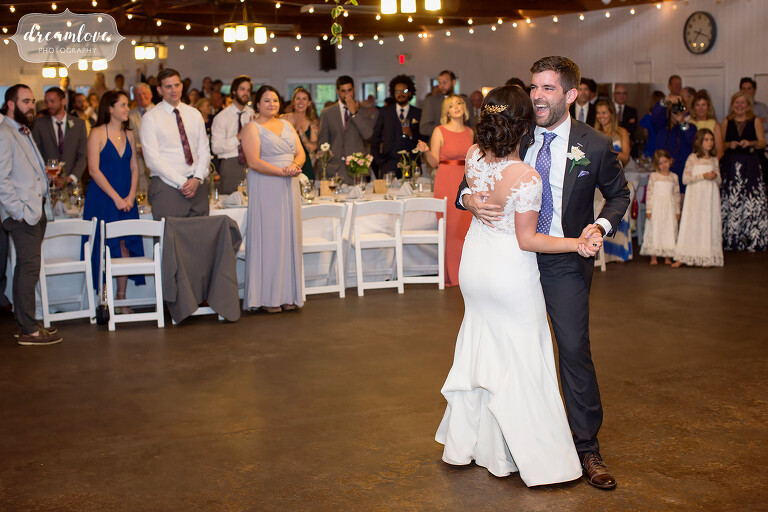 The bride and groom have their first dance in the mess hall at this NY camp wedding.