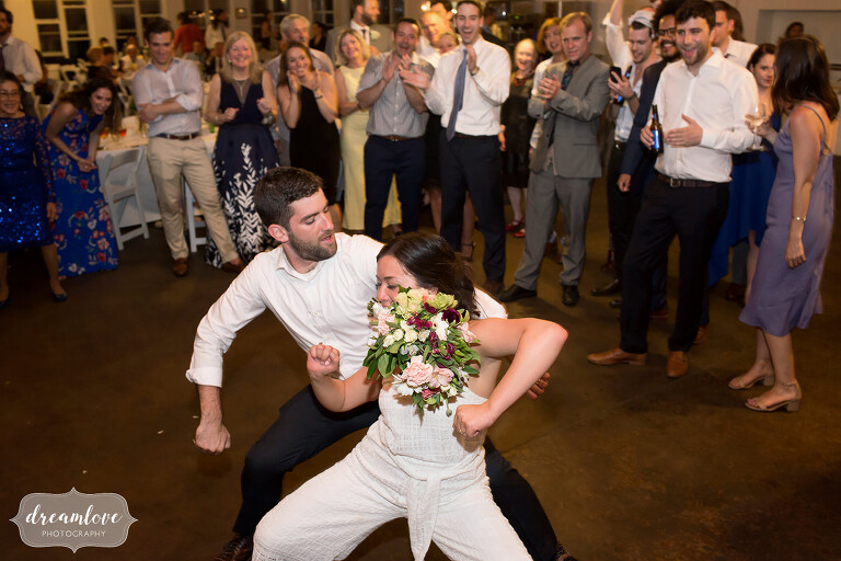 The bride holds her bouquet in her teeth while dancing in a white jumpsuit at NY camp wedding.
