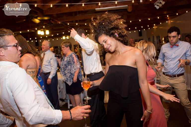 A girl throws her hair into the air while dancing at NY camp wedding.
