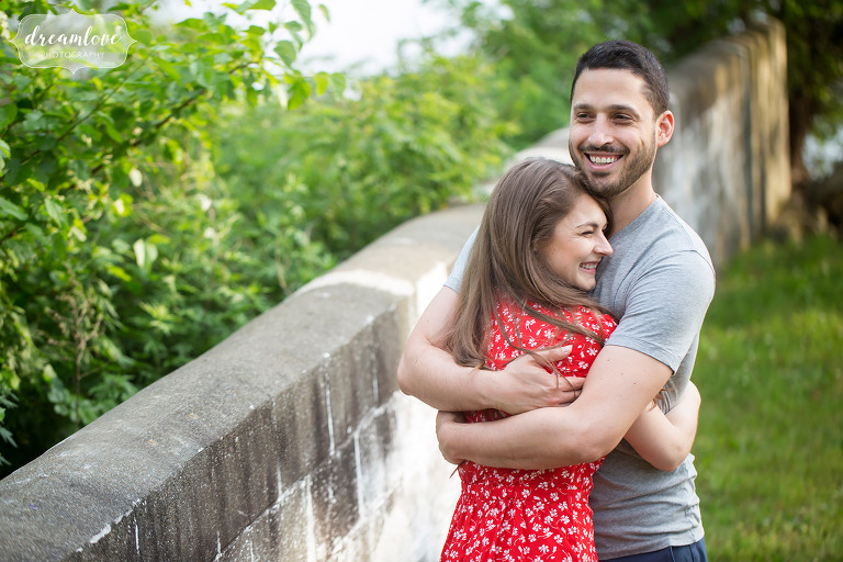 Couple hugs by Hudson River during their Hudson Valley engagement photo session in Cold Spring, NY.