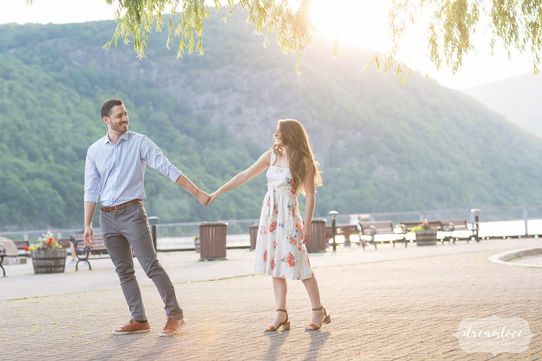 Ethereal engagement photos of the guy pulling the girl along the Hudson River in Cold Spring, NY.