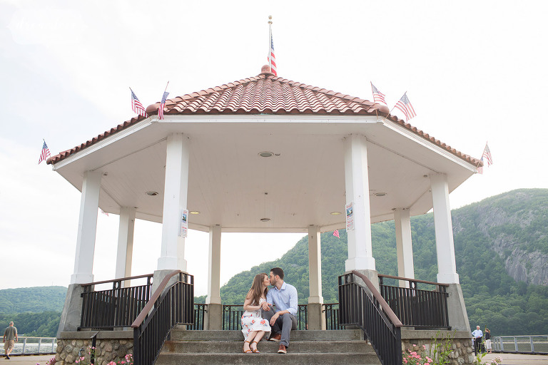 Couple kissing under the gazebo in Cold Spring, NY during their Hudson Valley engagement session in mid-June.