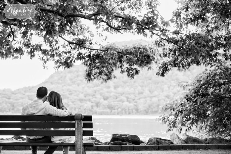 Classic black and white engagement photo of the couple on the bench talking in Cold Spring, NY while looking at Hudson River.