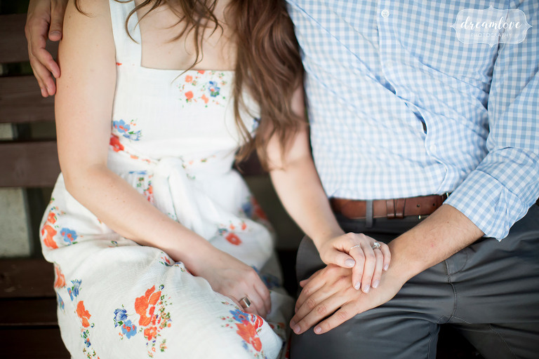 Natural engagement photos of couple's hands while sitting on bench in Cold Spring, NY.