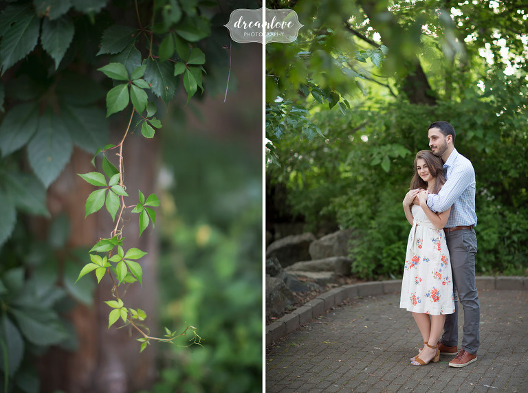 Couple stands in lush urban park for engagement photos in Cold Spring, NY.