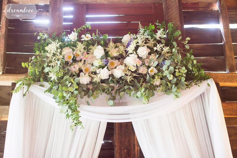 Rustic floral ceremony arbor for the inside barn at Bishop Farm in NH.