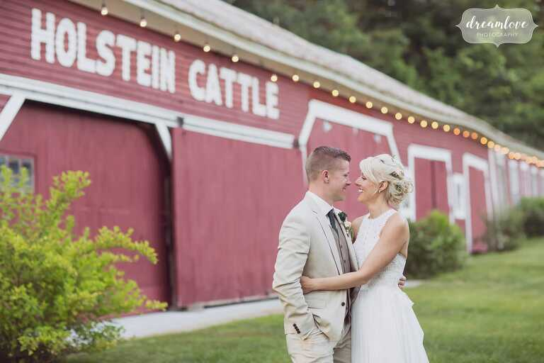 The bride and groom hug in front of the old red dairy barn at this woodsy Bishop Farm venue in NH.