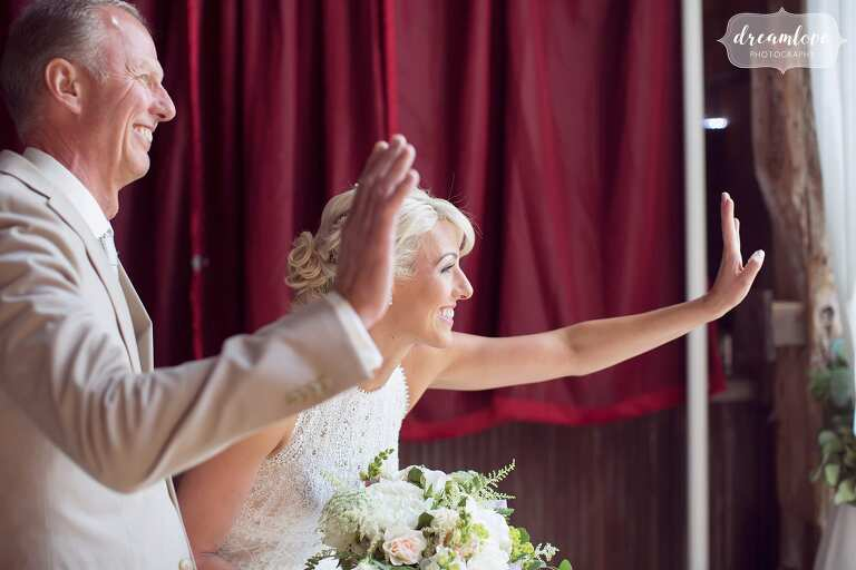 The bride and her father wave at guests for this Bishop Farm wedding.