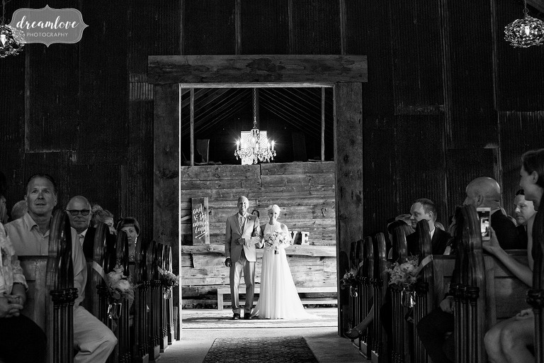 The bride and her father walk into the barn for the indoor wedding ceremony at Bishop Farm in NH.