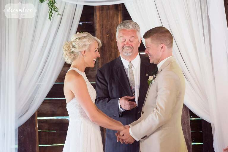 The bride and groom hold hands during barn wedding ceremony.