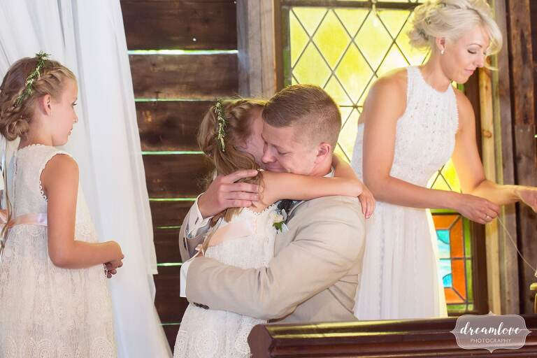 The groom hugs the bride's daughter during barn wedding ceremony.