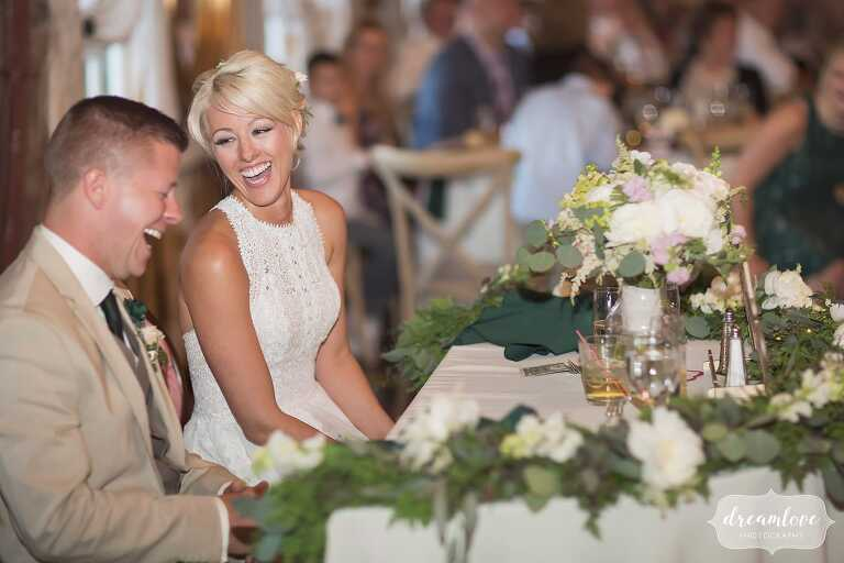 Natural wedding photos of bride and groom laughing during toasts at Bishop Farm.
