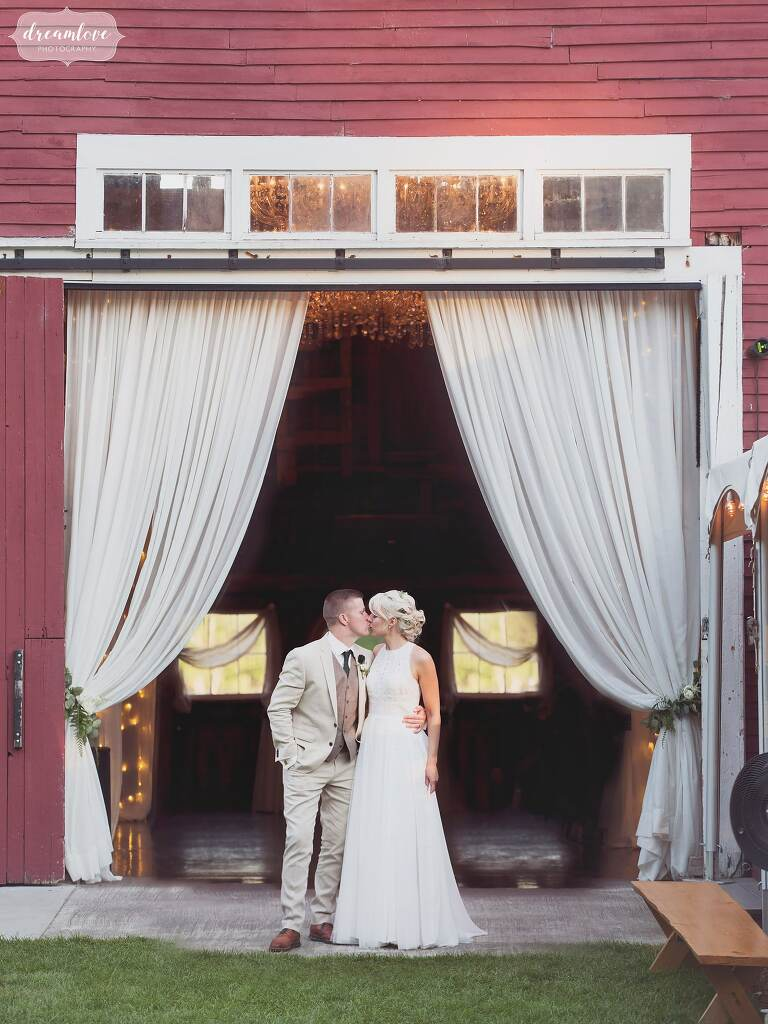 The bride and groom kiss in the barn doorway at Bishop Farm venue in NH.