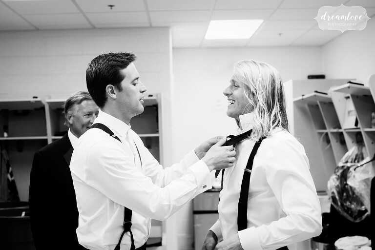 Documentary wedding photo of the best man helping the groom with bow tie in Central PA.