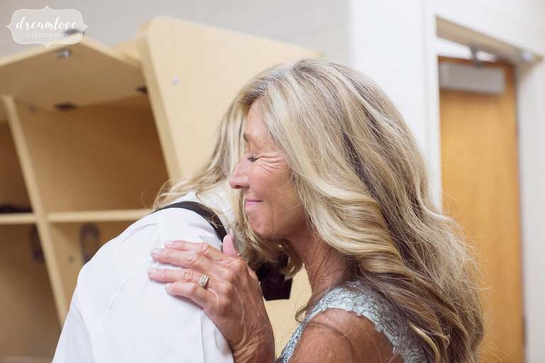 The mother of the groom gives her son a hug while he's getting ready.