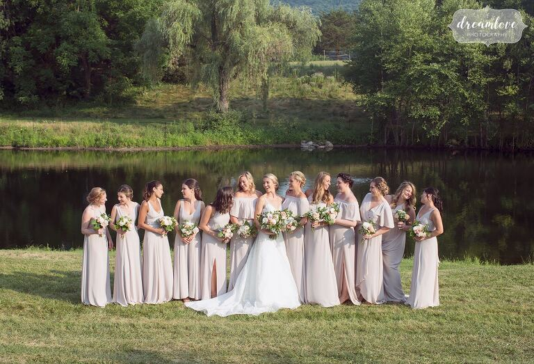 Lots of bridesmaids in front of pond at One Barn Farm.