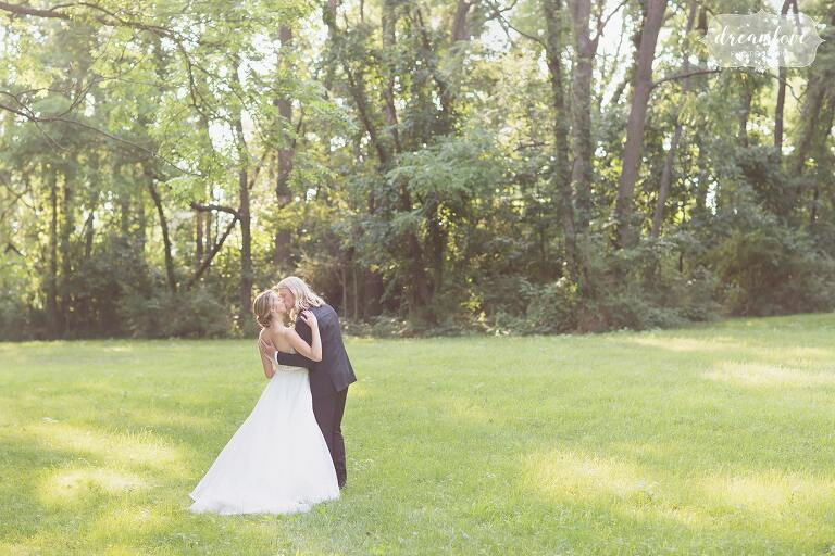 The bride and groom kiss in the field at One Barn Farm country venue in Miffinburg, PA.