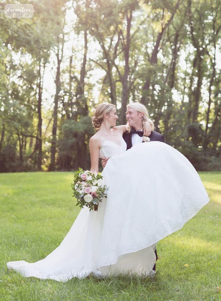 Fairytale wedding and groom carries bride at One Barn Farm.
