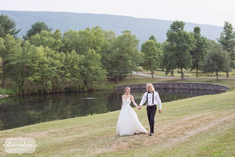 Candid wedding photos of the bride and groom holding hands at One Barn Farm.