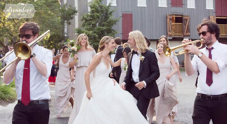 The bride and groom have a marching band procession with the Love Revival to their tented reception at One Barn Farm.