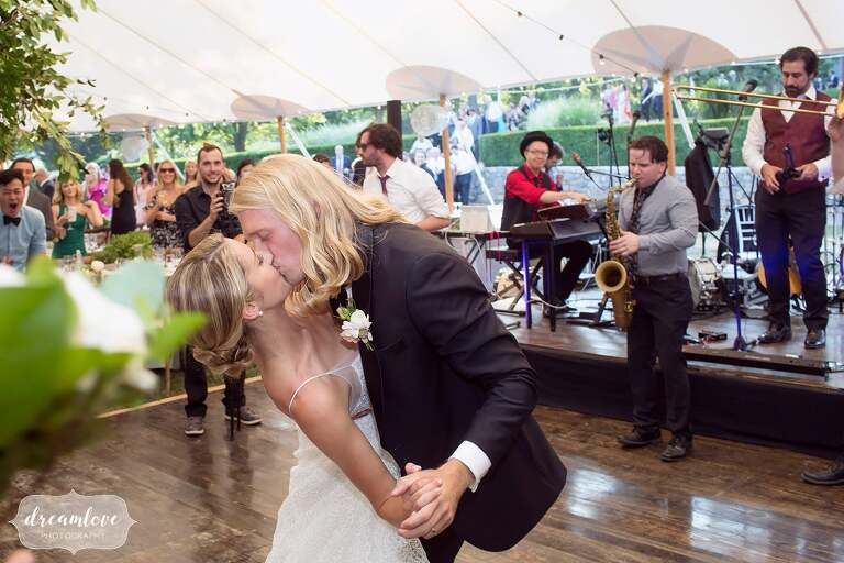 Bride and groom kiss after first dance under tent at One Barn Farm.