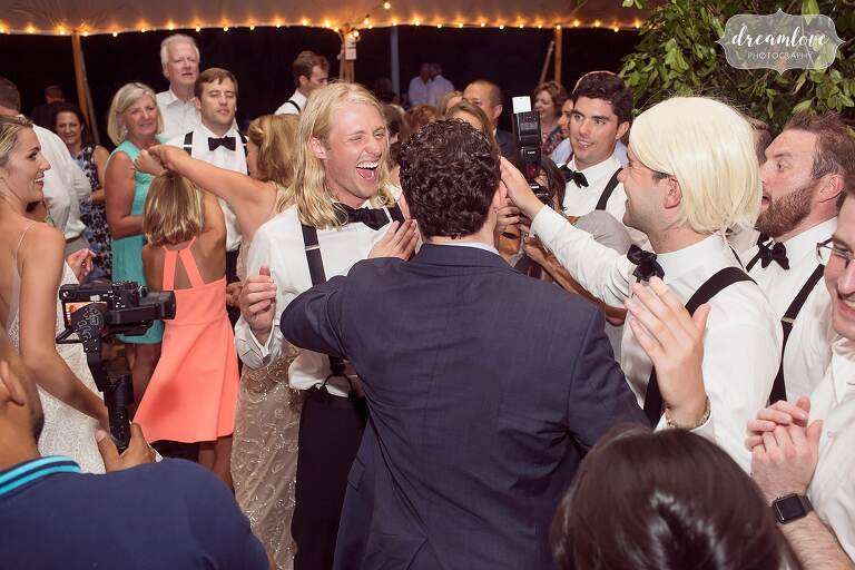 Groom laughing at One Barn Farm tented reception.