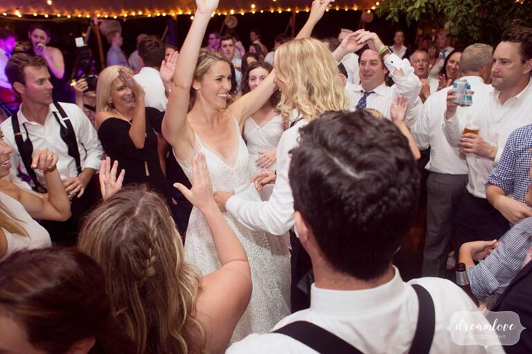 The bride throws her arms in the air at the end of this One Barn Farm wedding.