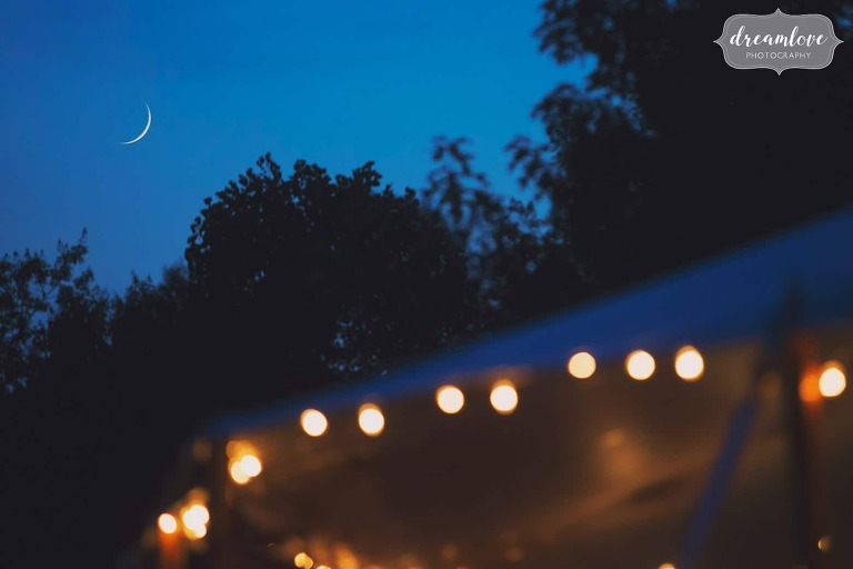 Crescent moon over cafe lights in reception tent with blue twilight.