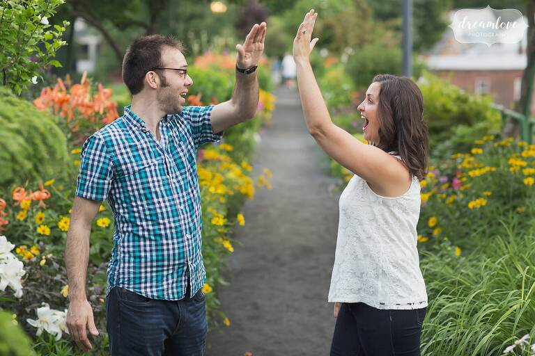 Couple high fives each other during a fun engagement photo session on the Bridge of Flowers in Shelburne Falls, MA.