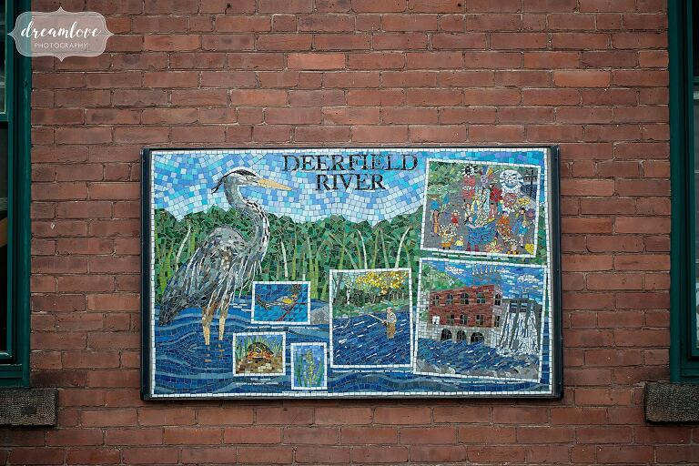 A tile mosaic sign of the Deerfield River during engagement photo shoot in Shelburne, MA.