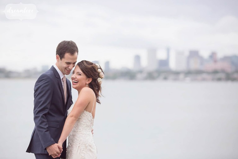 Bride and groom stand on the shore of their Boston Harbor wedding with the city skyline behind them.