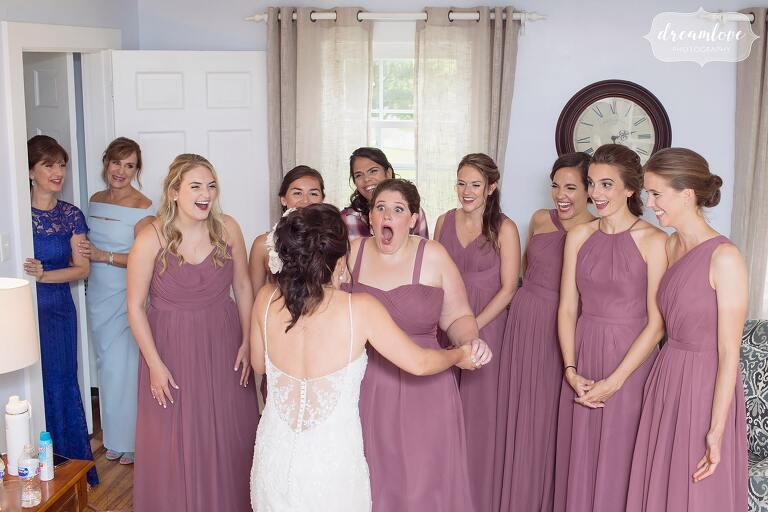 Best documentary wedding photo of the bridesmaids seeing bride in her dress on Thompson Island in Boston.