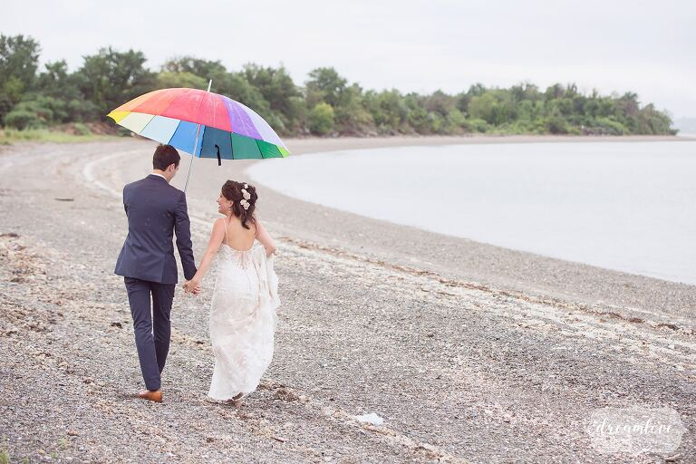 The bride and groom walk along the shore on Thompson Island with a rainbow umbrella.