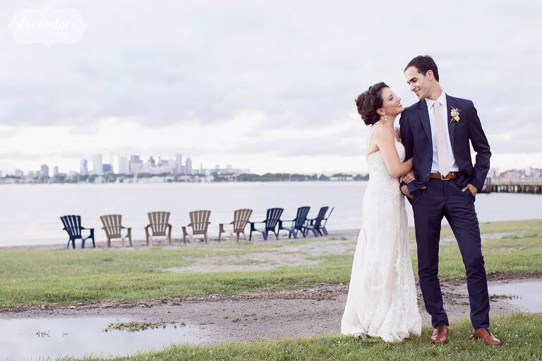 Bride and groom stand in front of chairs on Thompson Island.