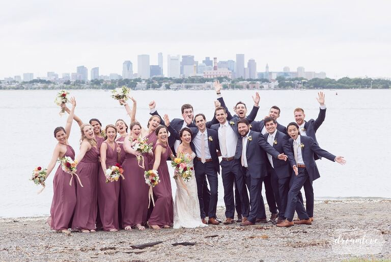 Wild wedding party on Thompson Island with Boston skyline behind them.