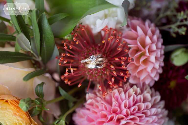 Artistic wedding photography of rings on protea flowers in Boston Harbor wedding.