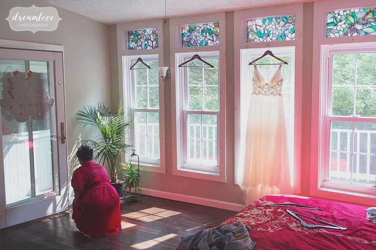 Bride wearing a red asian robe with her wedding dress hanging in window.