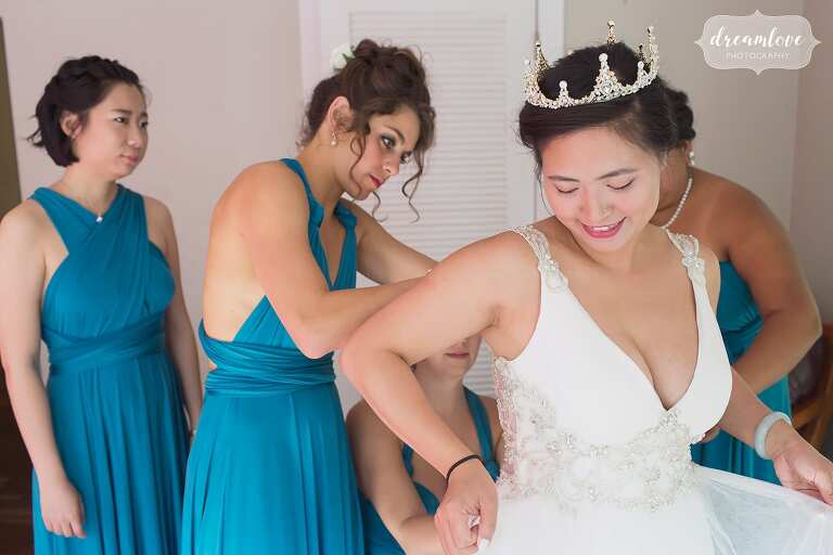 Bridesmaids help put the dress on in teal etsy dresses.