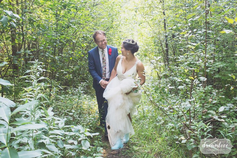 Bride and groom walk through a field in hunter blue boots.
