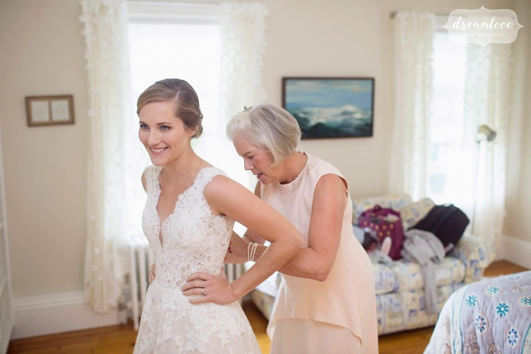Bride's mom helps her put on the wedding dress in Manchester-by-the-Sea.